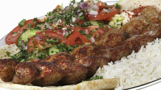 Lula kebab on rice with tomato and cucumber salad