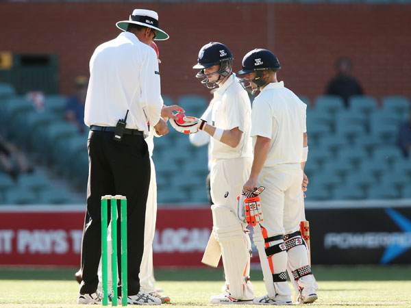Steve Smith (c) talks to the umpire about the pink ball during NSW's Sheffield Shield clash with South Australia. (Getty)