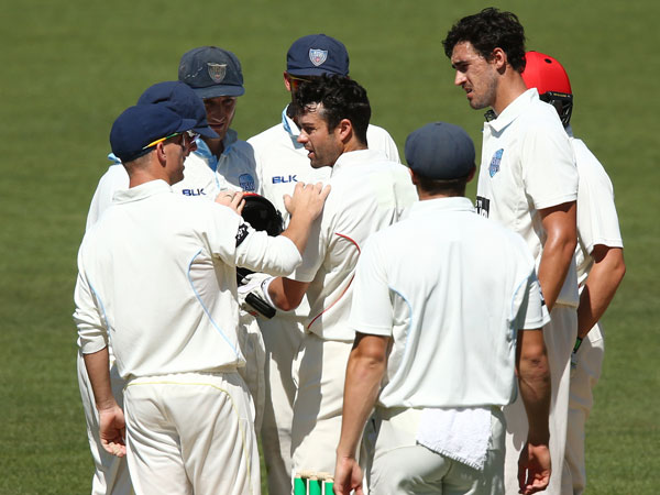 NSW players check on SA batsman Callum Ferguson after he was struck in the helmet by a Mitchell Starc bouncer. (Getty)