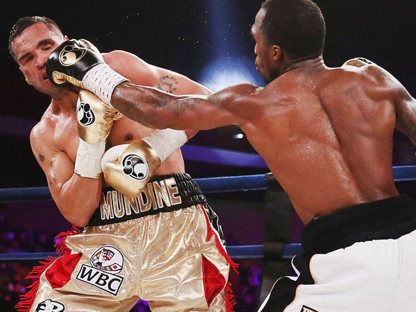 Anthony Mundine takes a hit against Charles Hartley. (Getty)