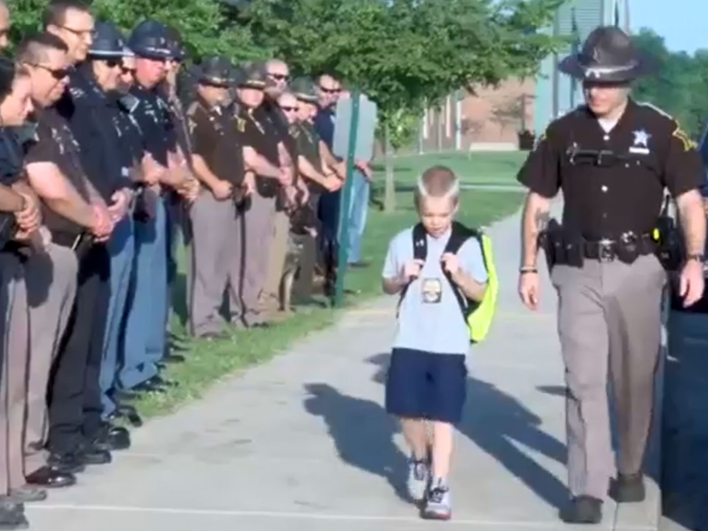 Dozens of police form guard of honour for boy whose father died
