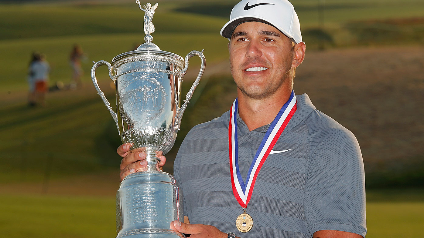Brooks Koepka holds up the Golf Champion Trophy after winning the U.S. Open in 2018