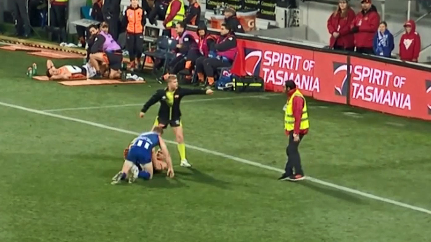 An AFL security guard steps onto the ground