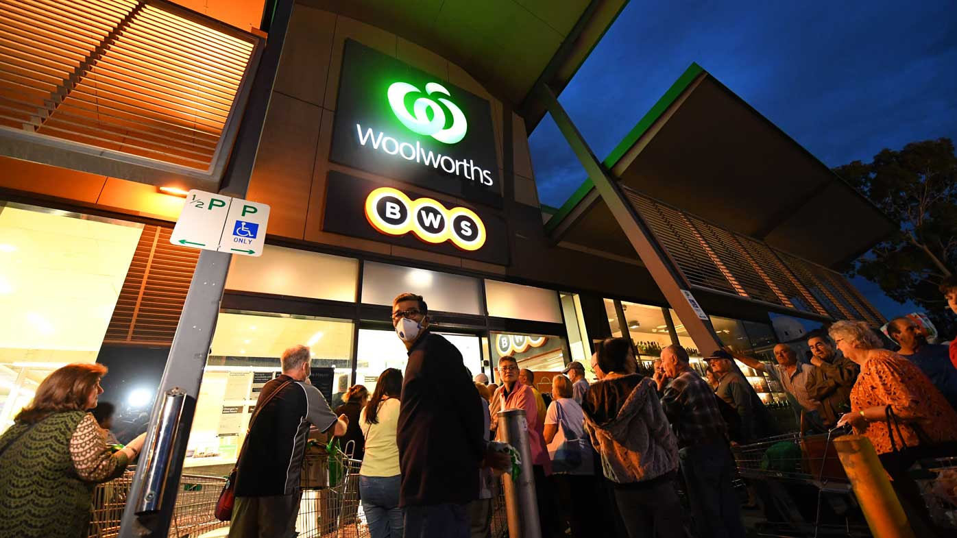 Shoppers queue up outside a Woolworths的 in Melbourne.