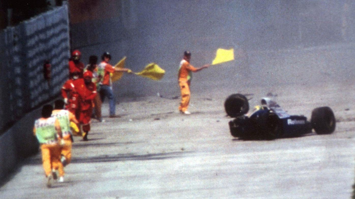 Officials run towards Ayrton Senna's crashed Williams at the 1994 San Marino Grand Prix.