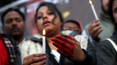 An Indian protester, with hands coloured in fake blood, holds a candle during a protest campaign. (AAP)