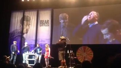 John Key eats bugs at a Bear Grylls show in Auckland.