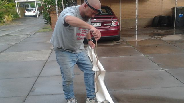 Snake catcher Mark Forgan catches a 1m snake which slithered under a baby car seat