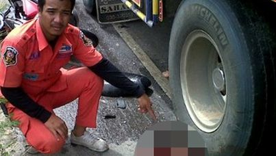 A Thai ambulance worker poses next to a dead body, in one of many graphic images posted on Facebook.
