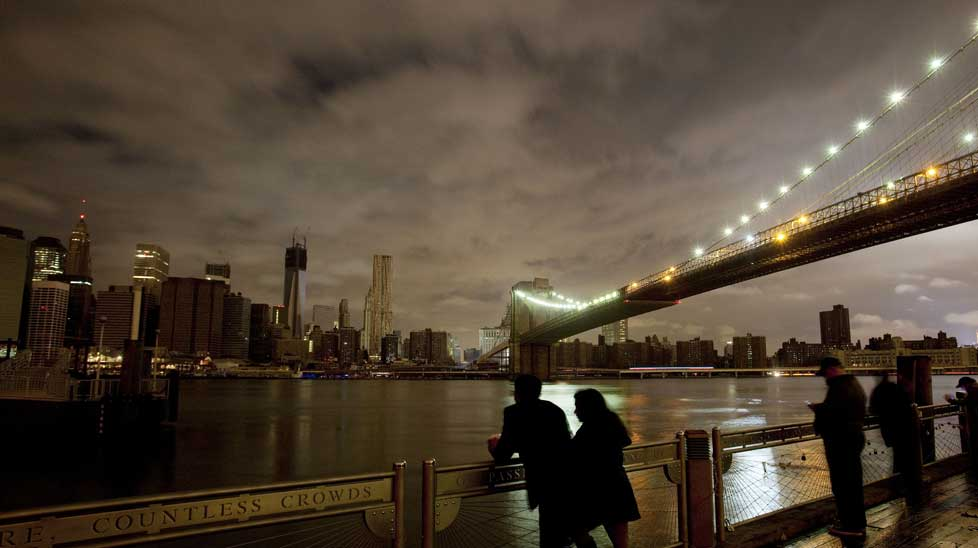 People stop along the Brooklyn waterfront to look at the dark Manhattan skyline. (AAP)
