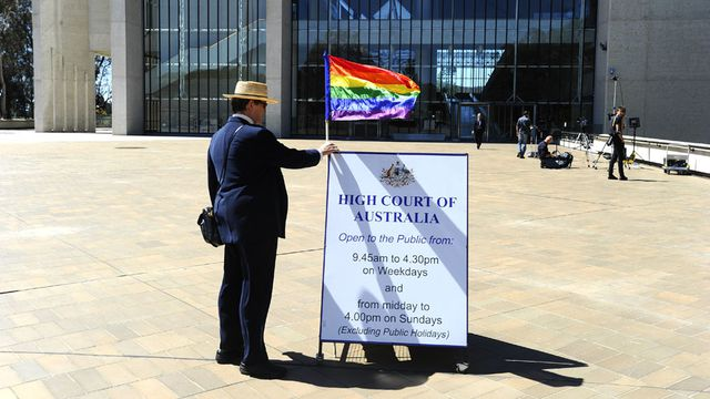 Marriage equality supporter stands outside the High Court in Canberra (AAP Image/Alan Porritt)