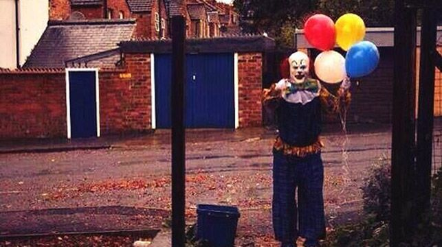 The creepy clown waives at photographer in Northampton.