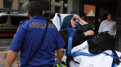 Rafah Mehanna is taken on a stretcher by ambulance officers from the Downing Centre Court in Sydney. An altercation broke out between the Mehana family and police just outside the door to the courtroom as their police assault charges were being heard. (AAP)