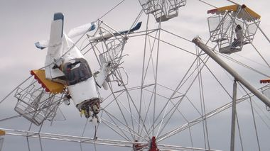 The pilot can be seen inside the light plane that crashed into a ferris wheel in Taree. (AAP)