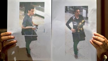 A Malaysian police official displays photographs of the two men who boarded the Malaysia Airlin