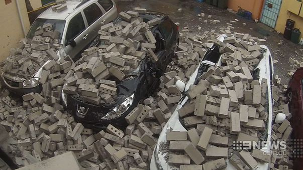 A brick wall was blown over onto some empty cars in Sydney. (9NEWS)