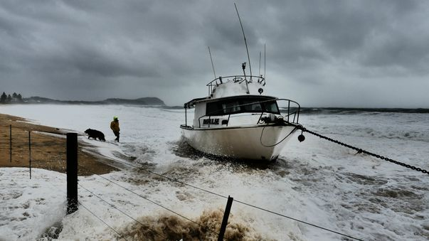 A man and his dog with a beached boat in Terrigal. (Tom Caska)