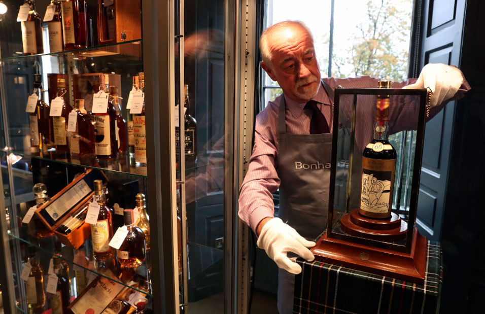 Danny McIlwraith, from Bonhams auction house, holds the bottle of The Macallan Valerio Adami during the auction in Edinburgh, Scotland.
