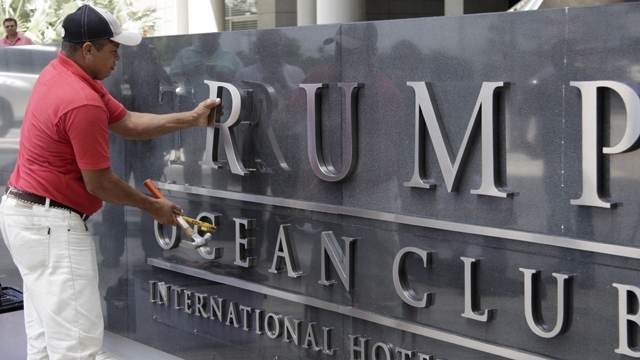A man removes the word Trump off a marquee outside the Trump Ocean Club International Hotel and Tower in Panama City.