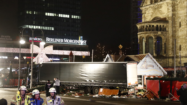 Police officers stand beside a truck which ran into a crowded Christmas market and killed several people in Berlin, Germany. (AAP)