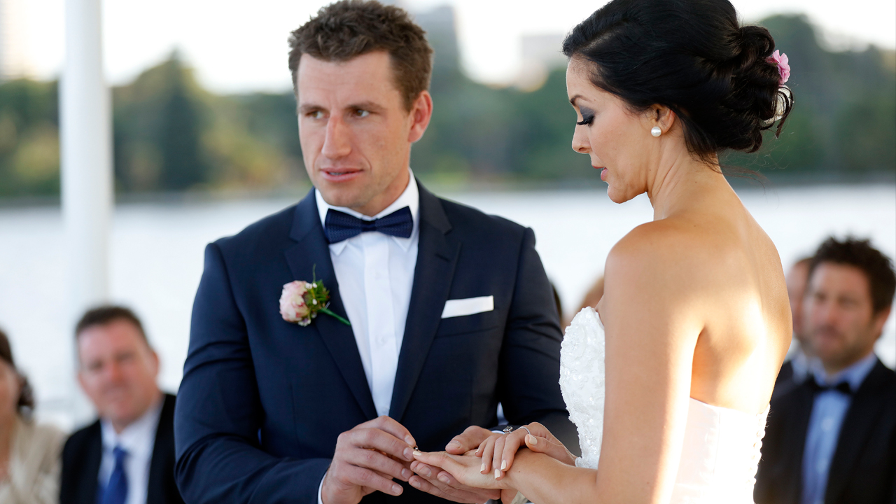 Mark asks the celebrant how to put a wedding ring on another human.
