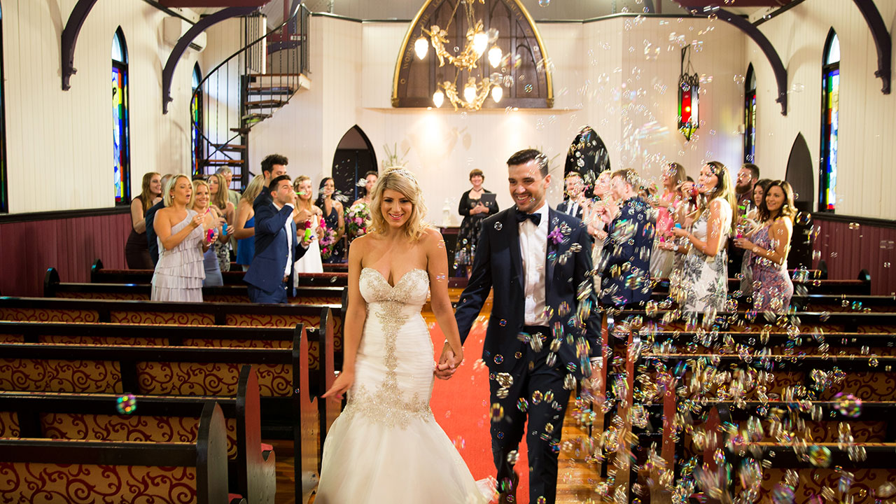 The couple, adorned in bubbles exit their ceremony.