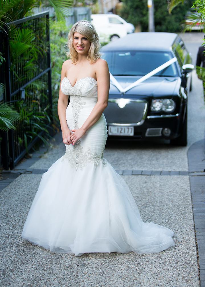 Bella poses in all her splendour in front of her wedding car.