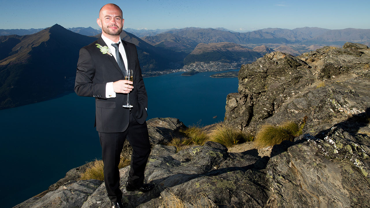 Having been delivered on the side of a mountain via helicopter, the grooms take some shots with champagne.