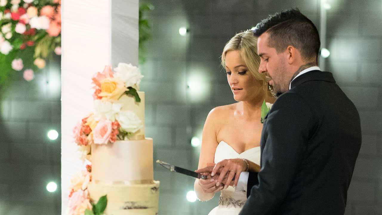 The new couple get ready to cut their floral cake.