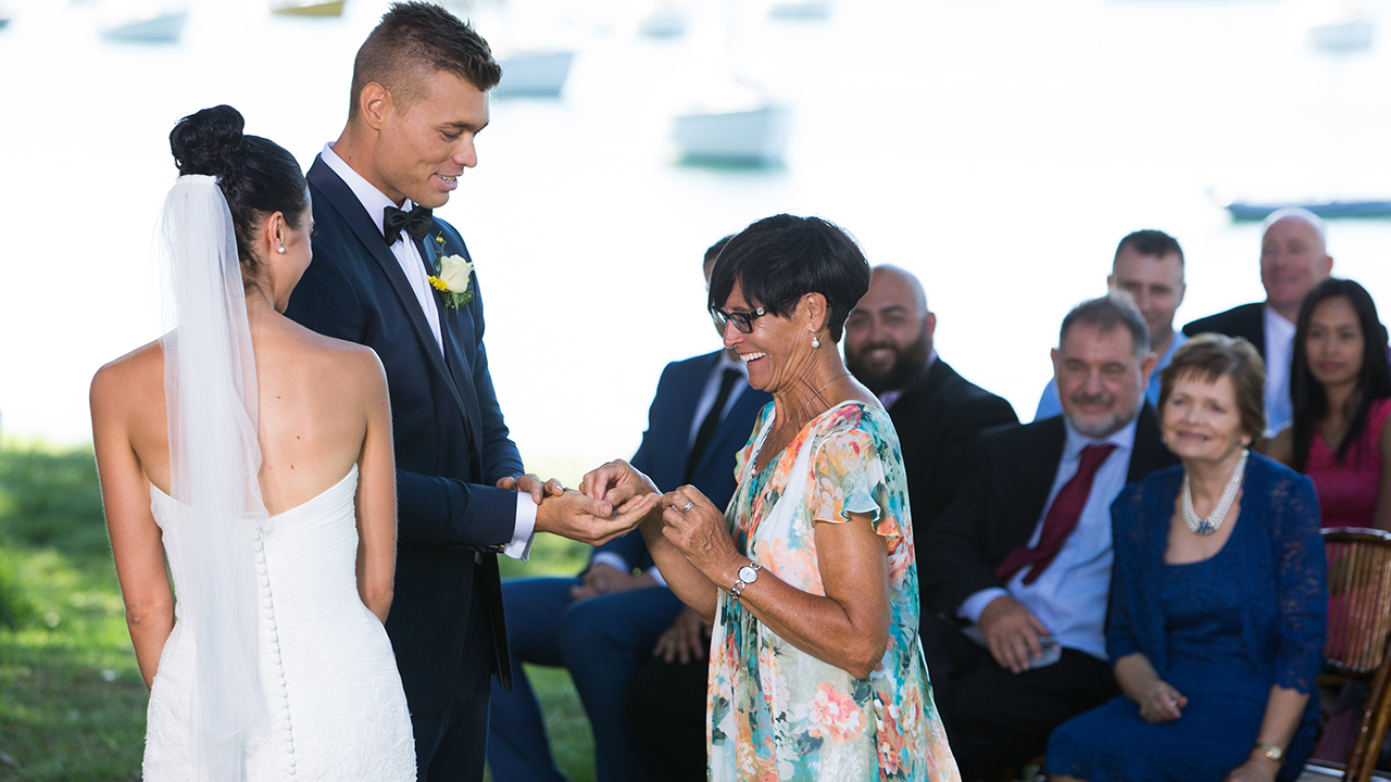 Monica's mother brings the rings to the couple.