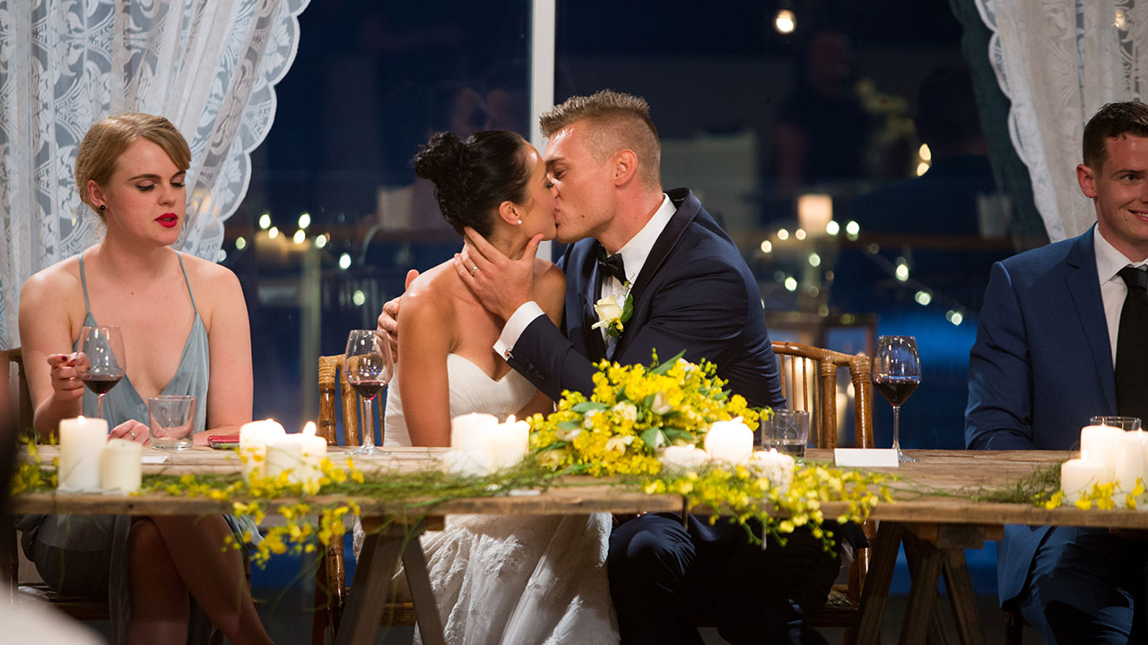 Monica and Mark embrace at their bridal table.