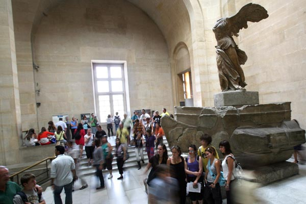 Tourists gather around the statue in the Louvre. (AAP)
