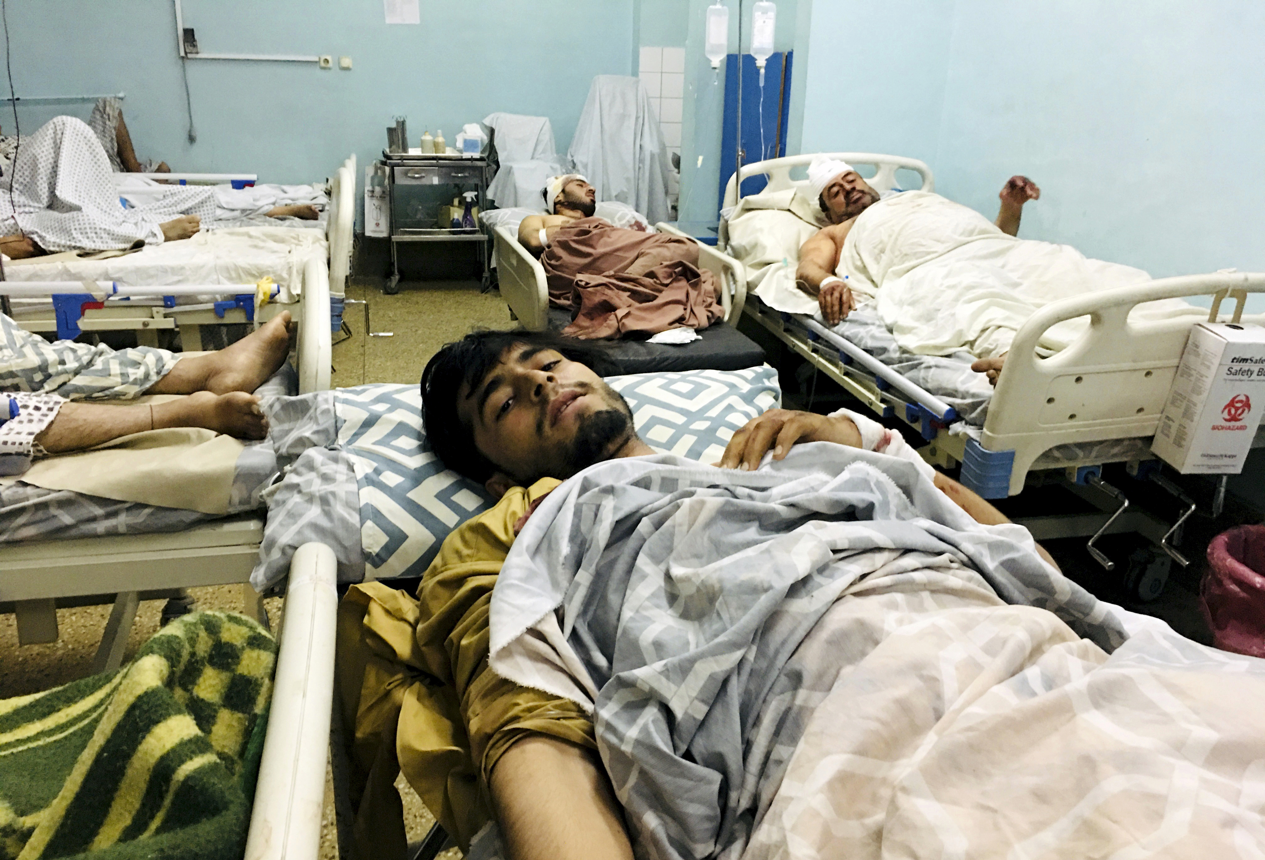 Wounded Afghans lie on a bed at a hospital after a deadly explosions outside the airport in Kabul, Afghanistan, Thursday, Aug. 26, 2021. Two suicide bombers and gunmen attacked crowds of Afghans flocking to Kabul's airport Thursday, transforming a scene of desperation into one of horror in the waning days of an airlift for those fleeing the Taliban takeover. The attacks killed at least 60 Afghans and 12 U.S. troops, Afghan and U.S. officials said. (AP Photo/Mohammad Asif Khan)