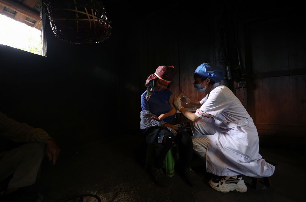 A medical worker provides a villager with door-to-door COVID-19 vaccination service at Danzhai County on August 28, 2021 in Qiandongnan Miao and Dong Autonomous Prefecture, Guizhou Province of China. (Photo by Huang Xiaohai/VCG via Getty