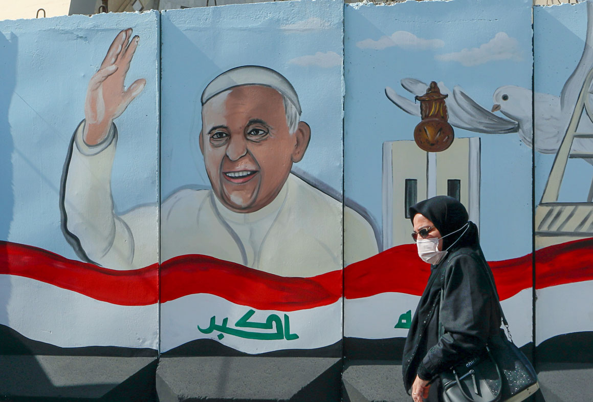 A woman walks past a mural depicting Pope Francis on a concrete wall placed by Iraqi security forces to surround the Our Lady of Salvation Church during preparations for the Pope's visit in Baghdad, Iraq, Monday, March 1, 2021