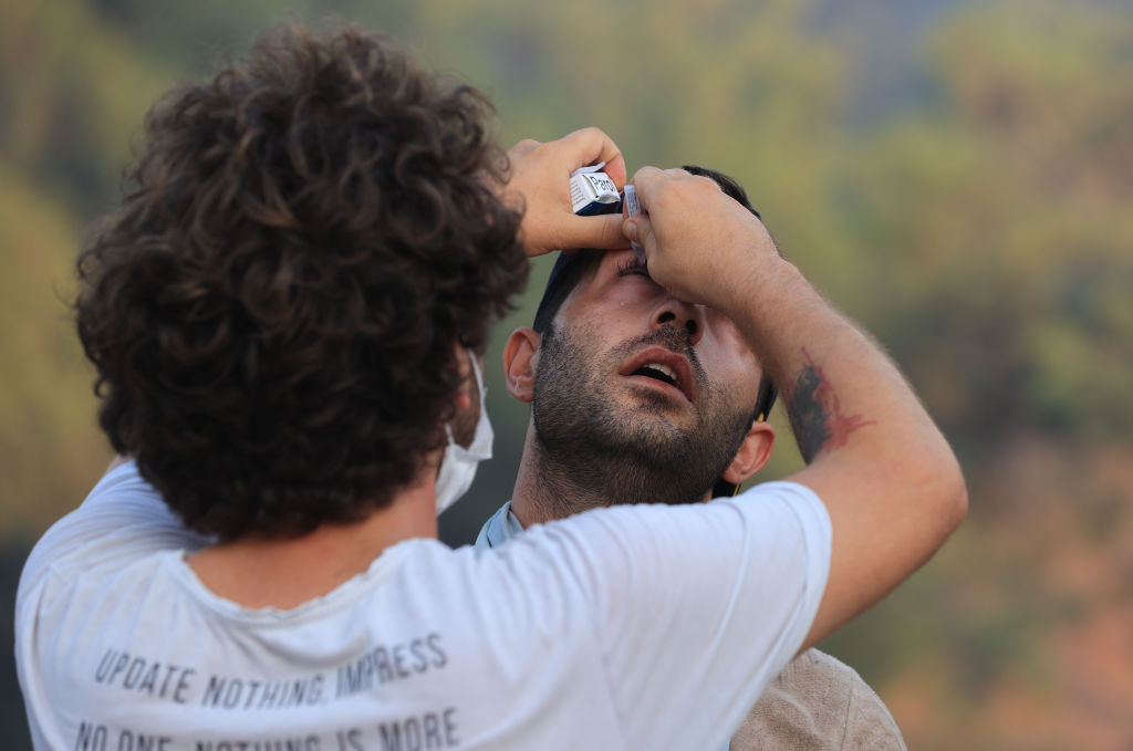A man applies eye drop to a fire-affected man. Turkish authorities maintain their tireless efforts to contain forest fires that erupted in various parts of the country. (Photo by Mahmut Serdar Alakus/Anadolu Agency via Getty Images)