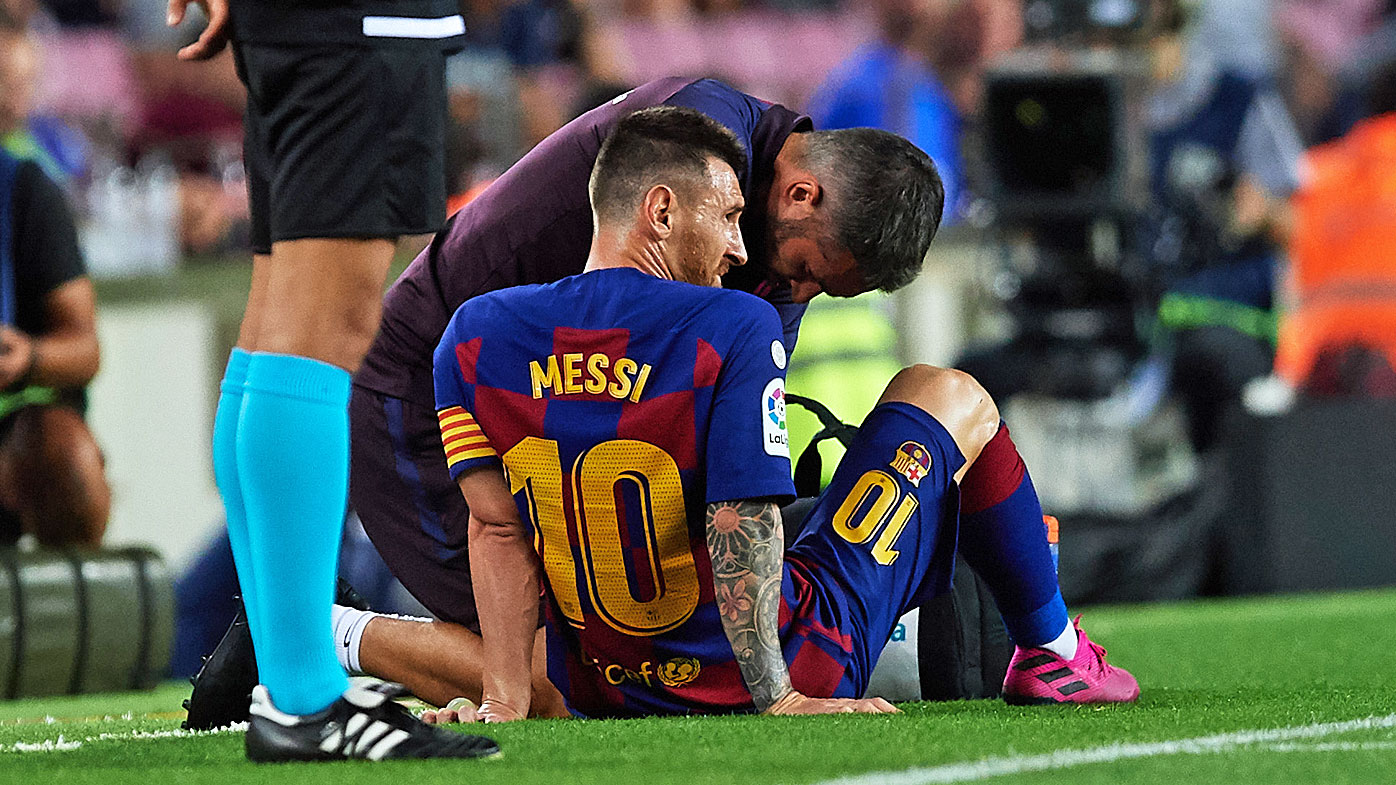 Lionel Messi of FC Barcelona receives medical treatment