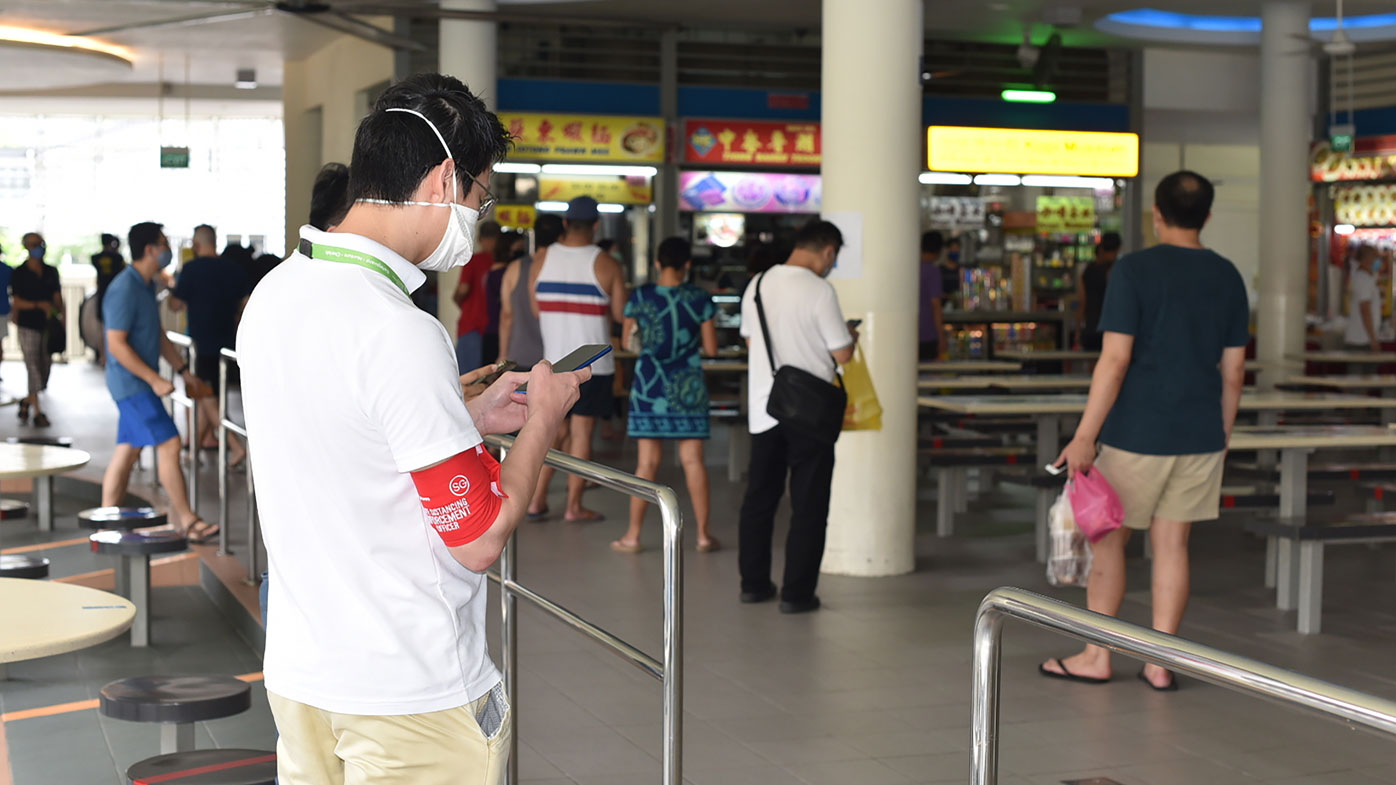 A safe-distancing enforcement officer wearing a red armband checks his phone at a food court in Singapore.