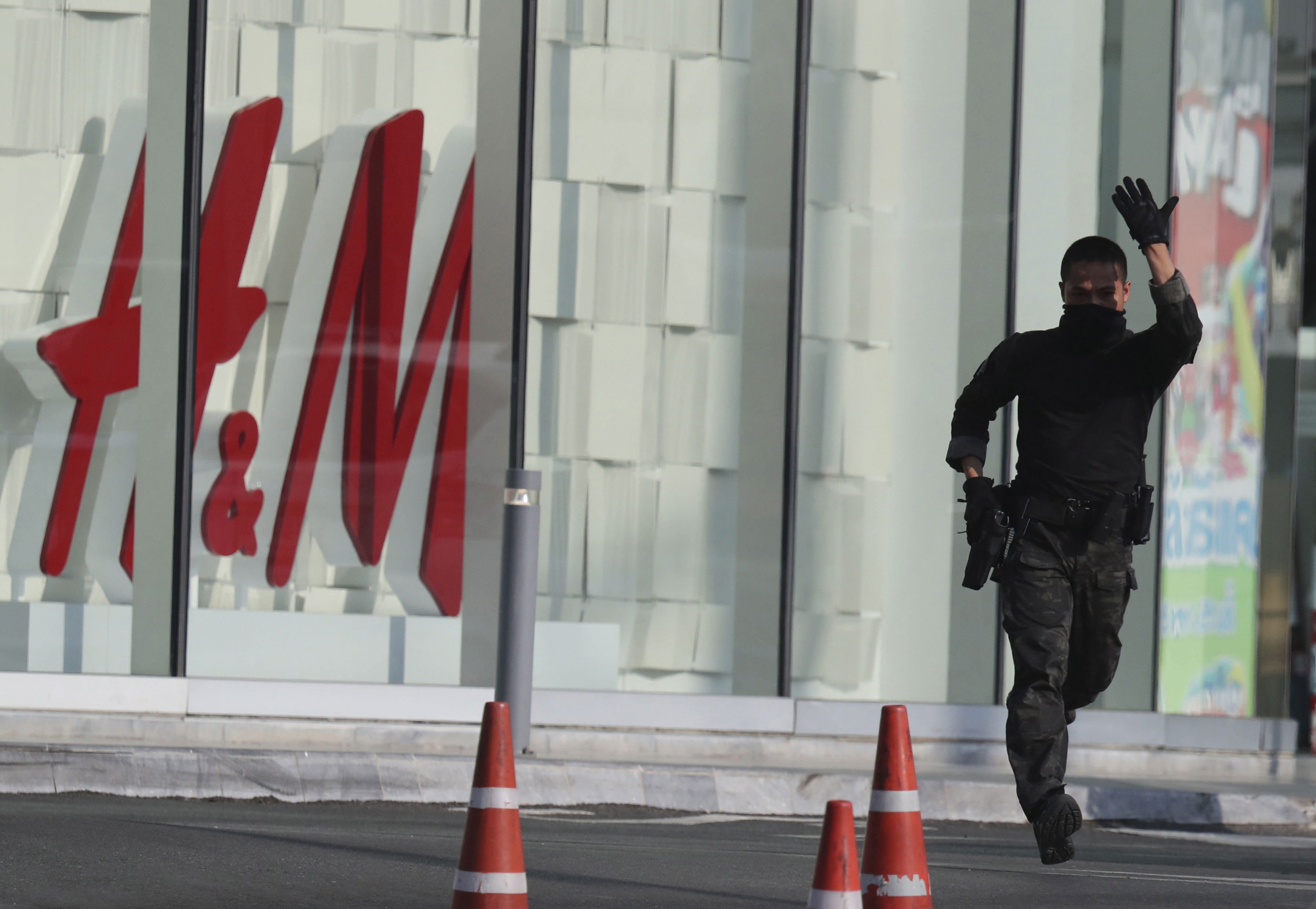 An armed commando soldier shouts for ambulance outside Terminal 21 Korat mall in Nakhon Ratchasima