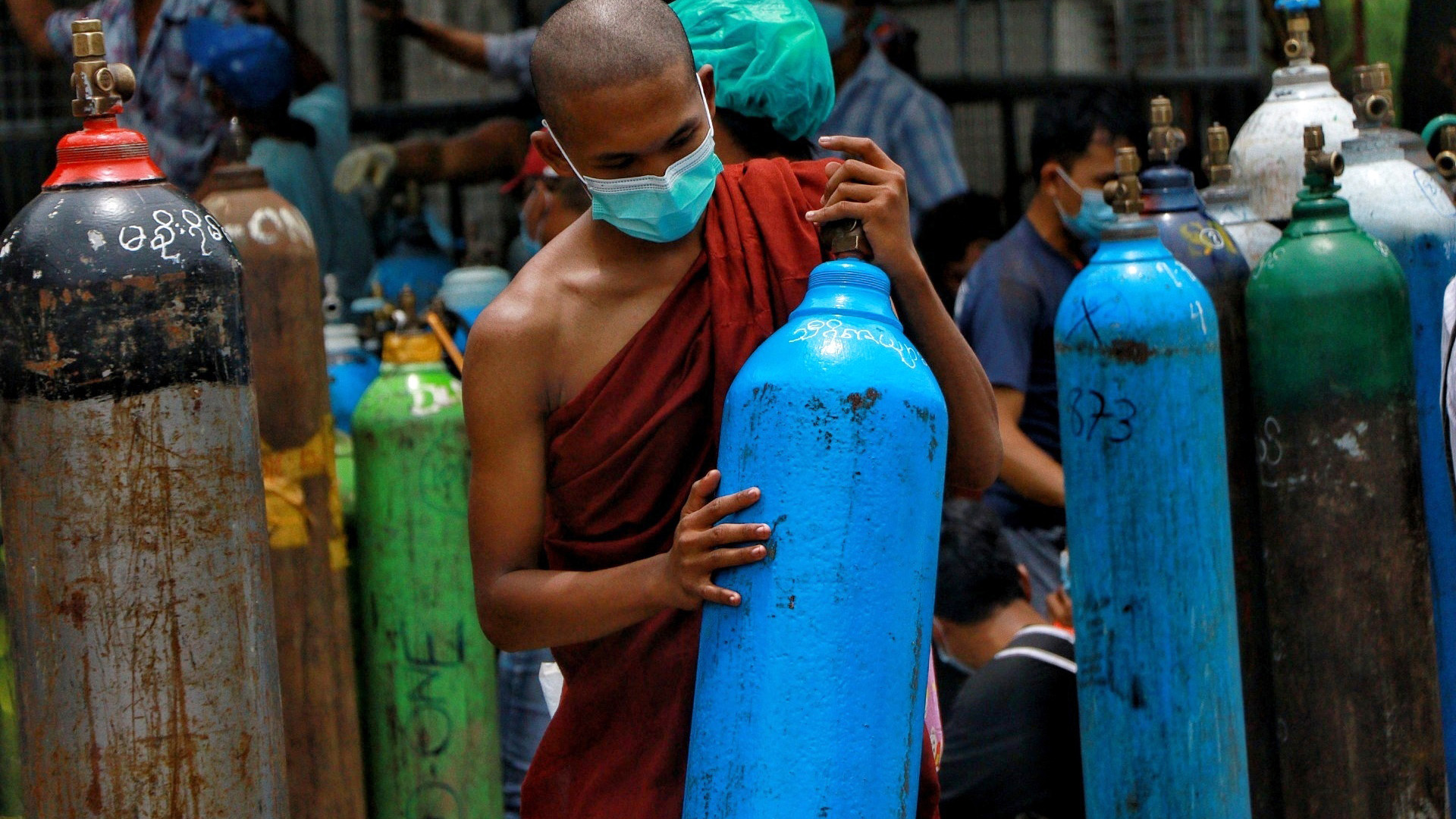 In this July 28, 2021, file photo, Buddhist monk wearing a face mask holds an oxygen tank for refill outside the Naing oxygen factory at the South Dagon industrial zone in Yangon, Myanmar.