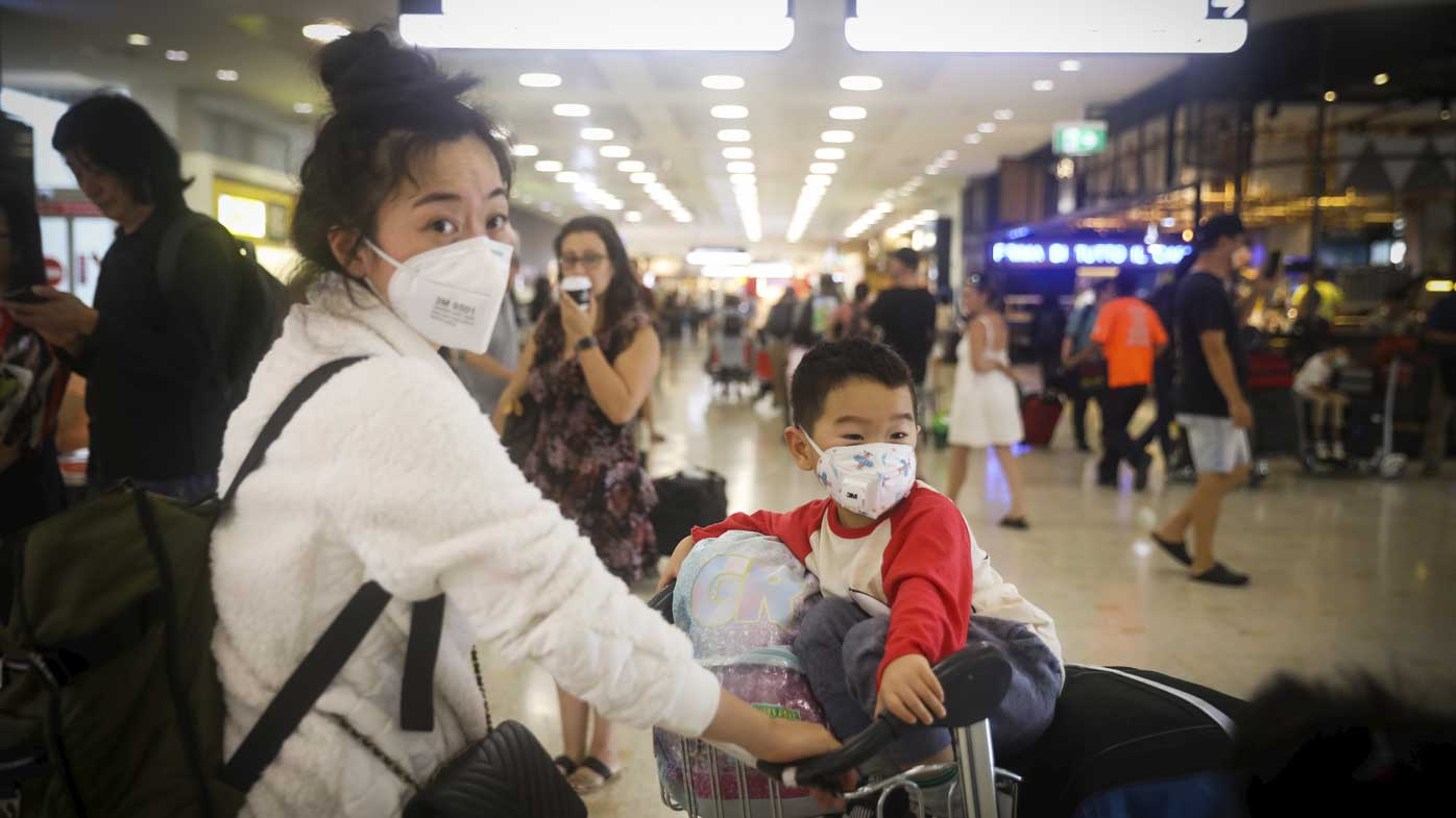 People arrive wearing masks to avoid contact with the Coronavirus at Sydney Airport.