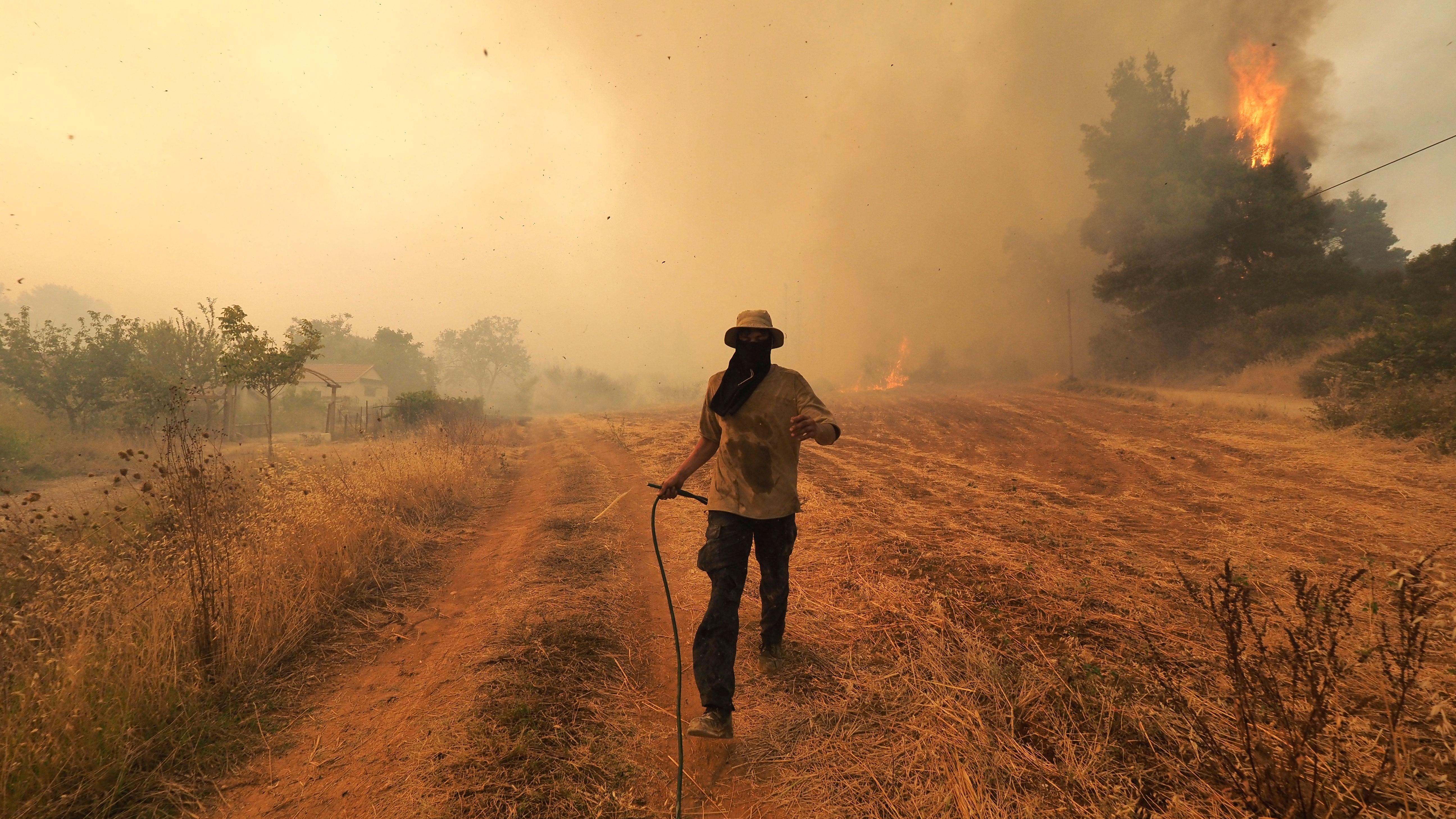 A man runs as fire burns trees in Kirinthos village on the island of Evia.
