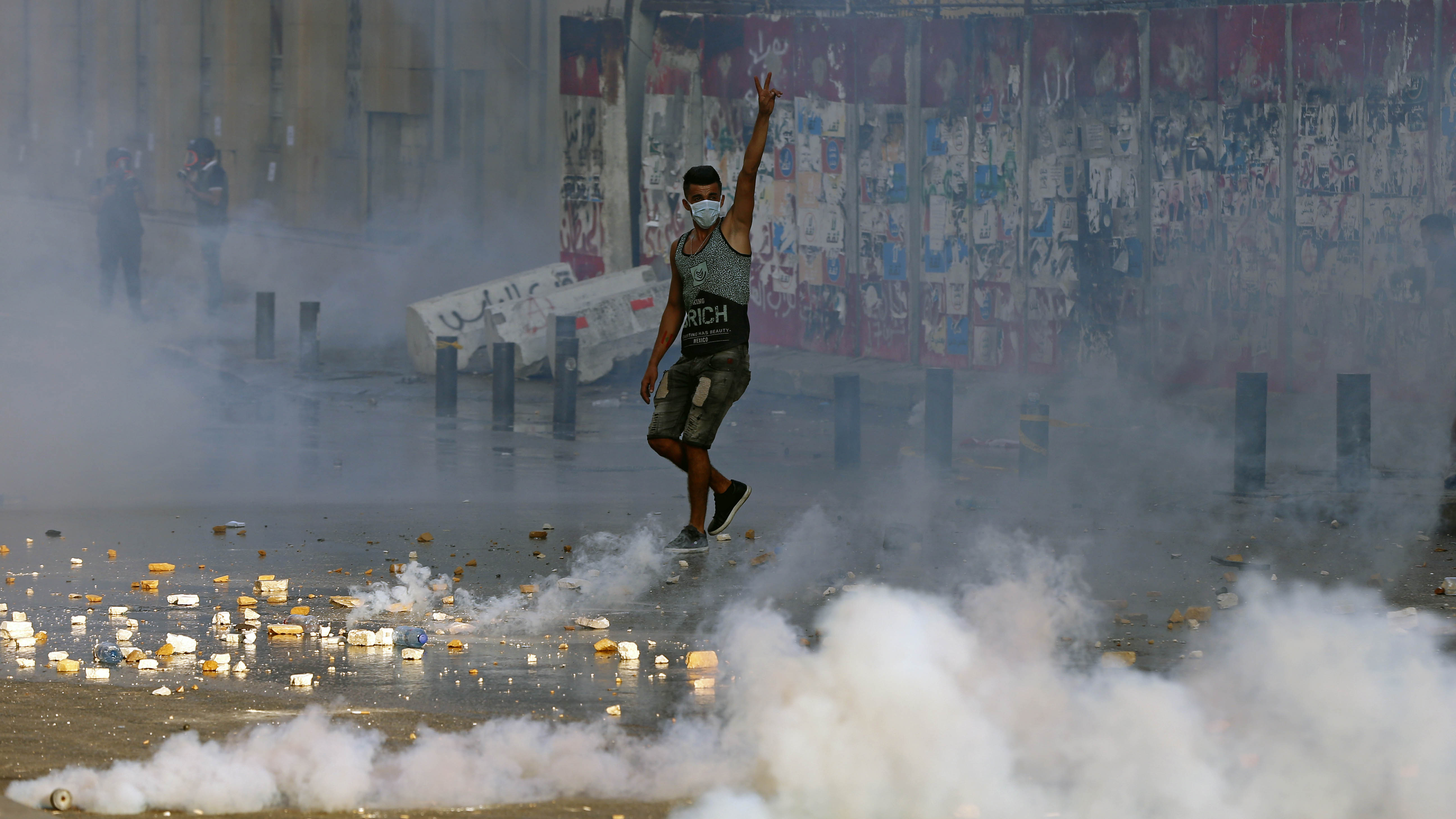 An anti-government protester flashes the victory sign amid tear gas fired by riot police during a protest marking the first anniversary of the massive blast at Beirut's port.