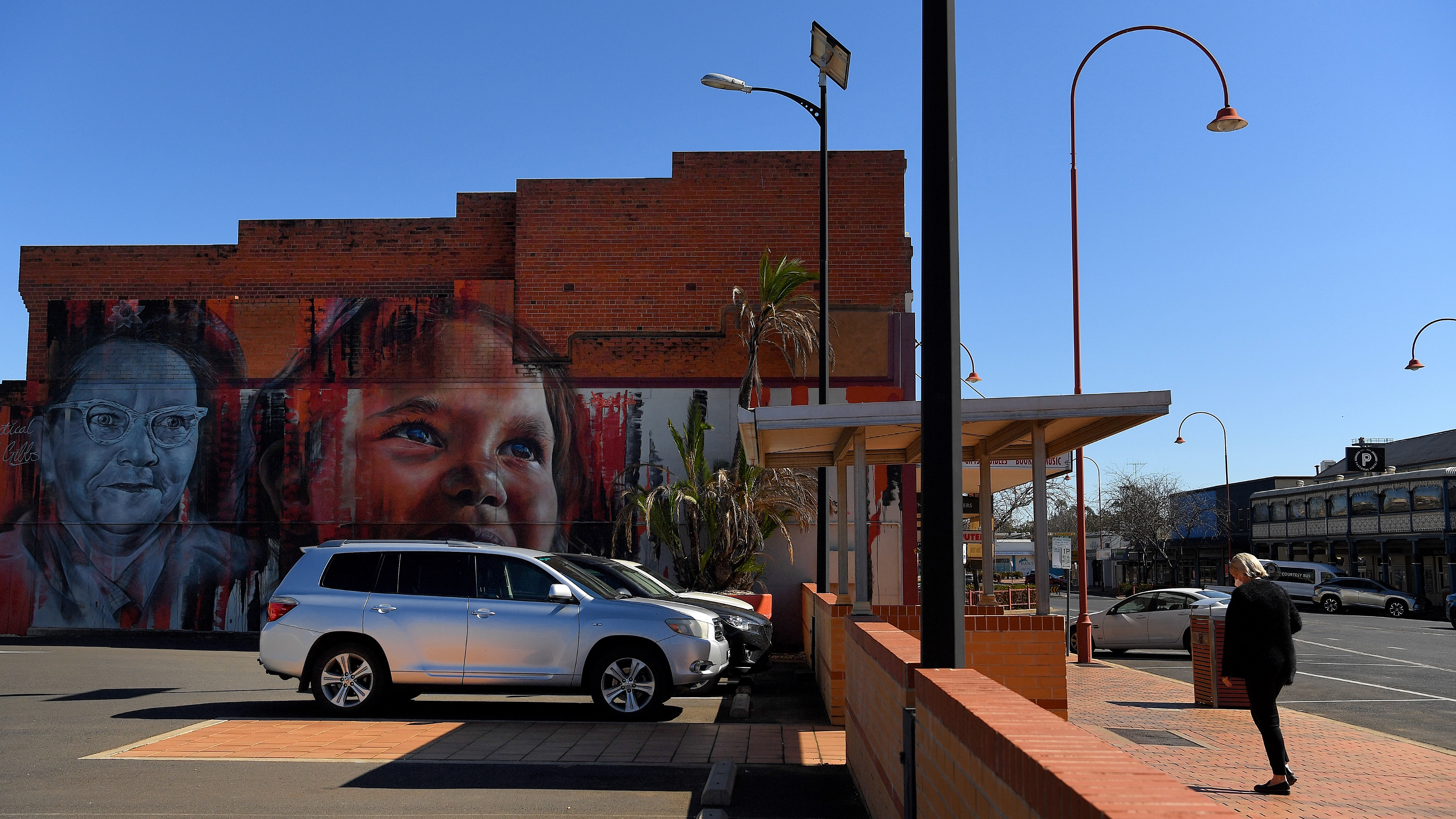 During the statewide lockdown a woman walks past a mural on the side of a building on Talbragar street in Dubbo, NSW.