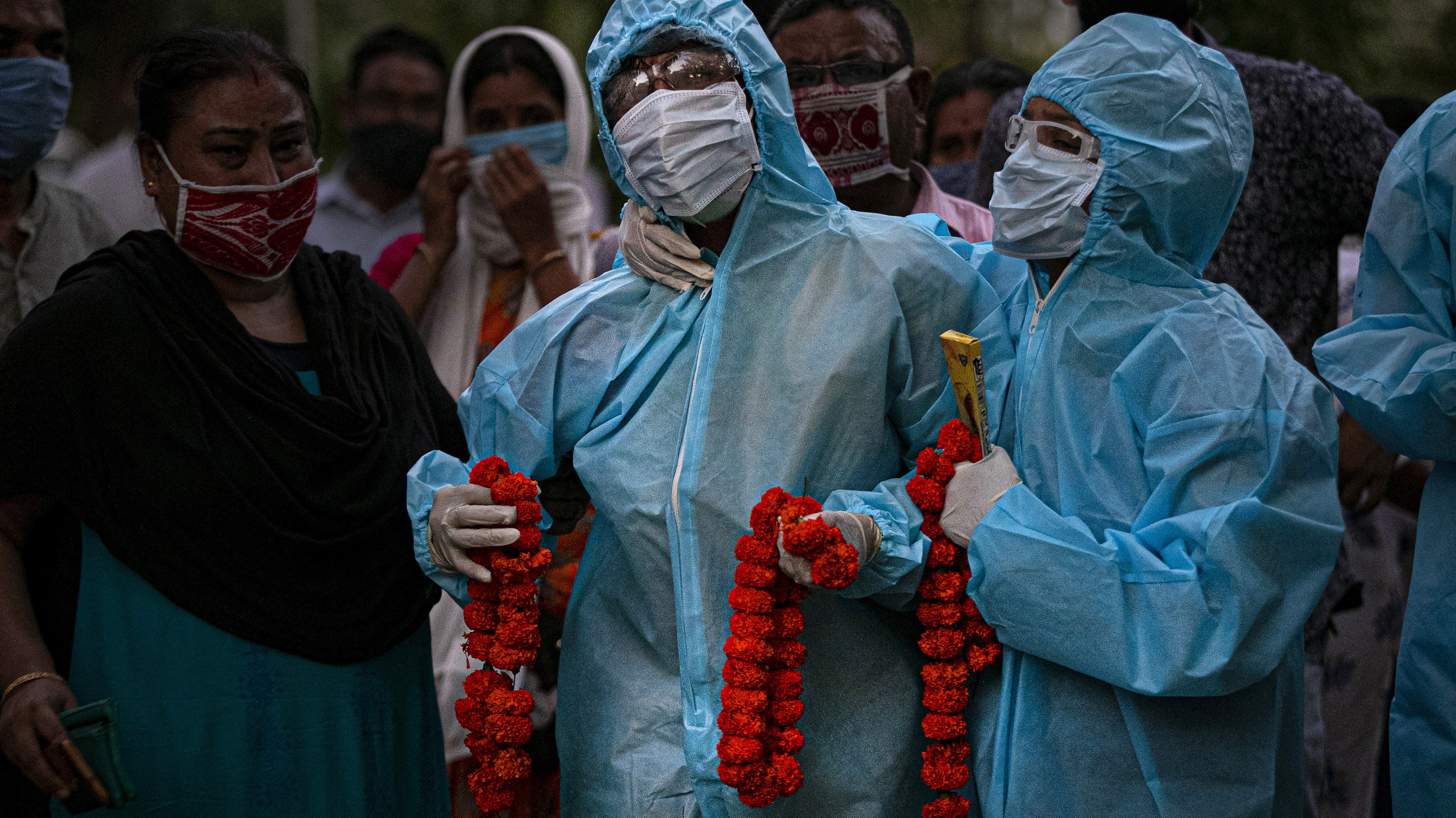 Relatives assist an Indian woman in personal protective equipment offer marigold garlands on the body of her husband  who died of COVID-19 in Gauhati, India,