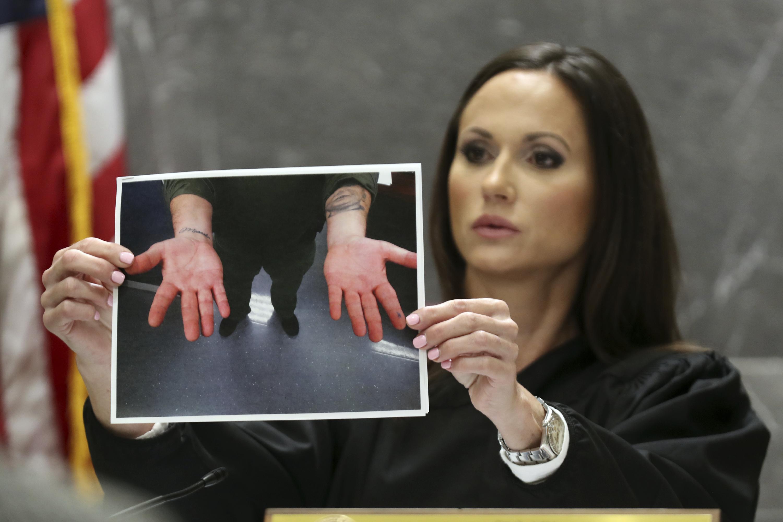 Judge Elizabeth Scherer holds a photograph of the hands of Broward jail guard Sgt. Ray Beltran after a November 2018 altercation between Beltran and Parkland school shooter Nikolas Cruz.