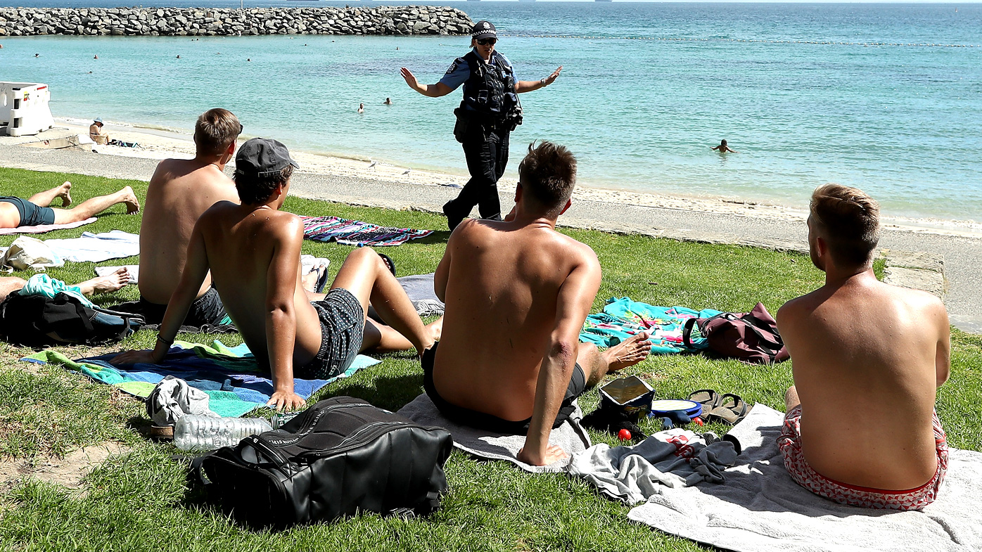 A Western Australia Police officer reminds men at a beach of social distancing requirements.