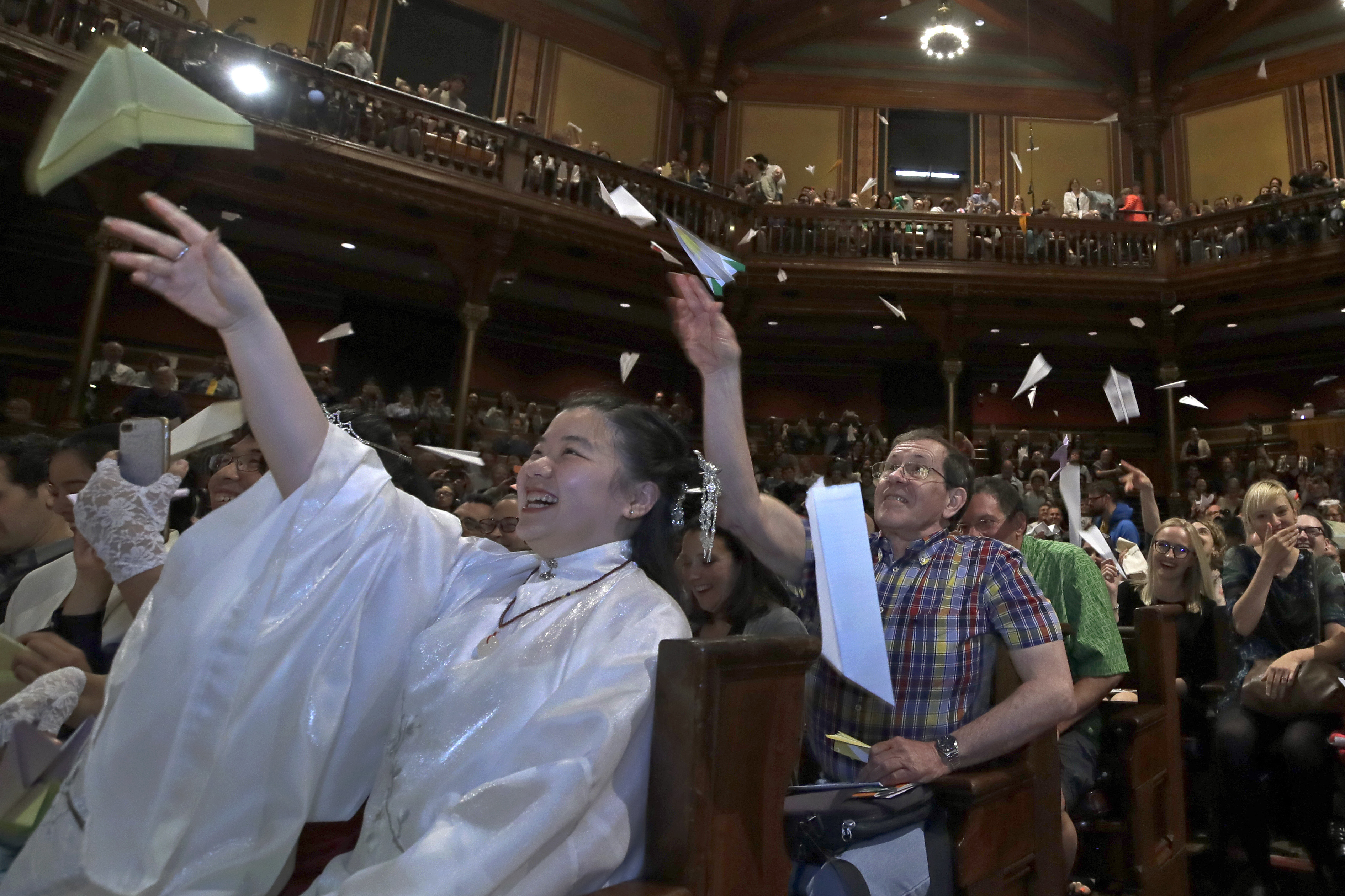 In this September 12, 2019 file photo, audience members toss paper airplanes at the 29th annual Ig Nobel awards ceremony at Harvard University, in Cambridge. (AP Photo/Elise Amendola, File)