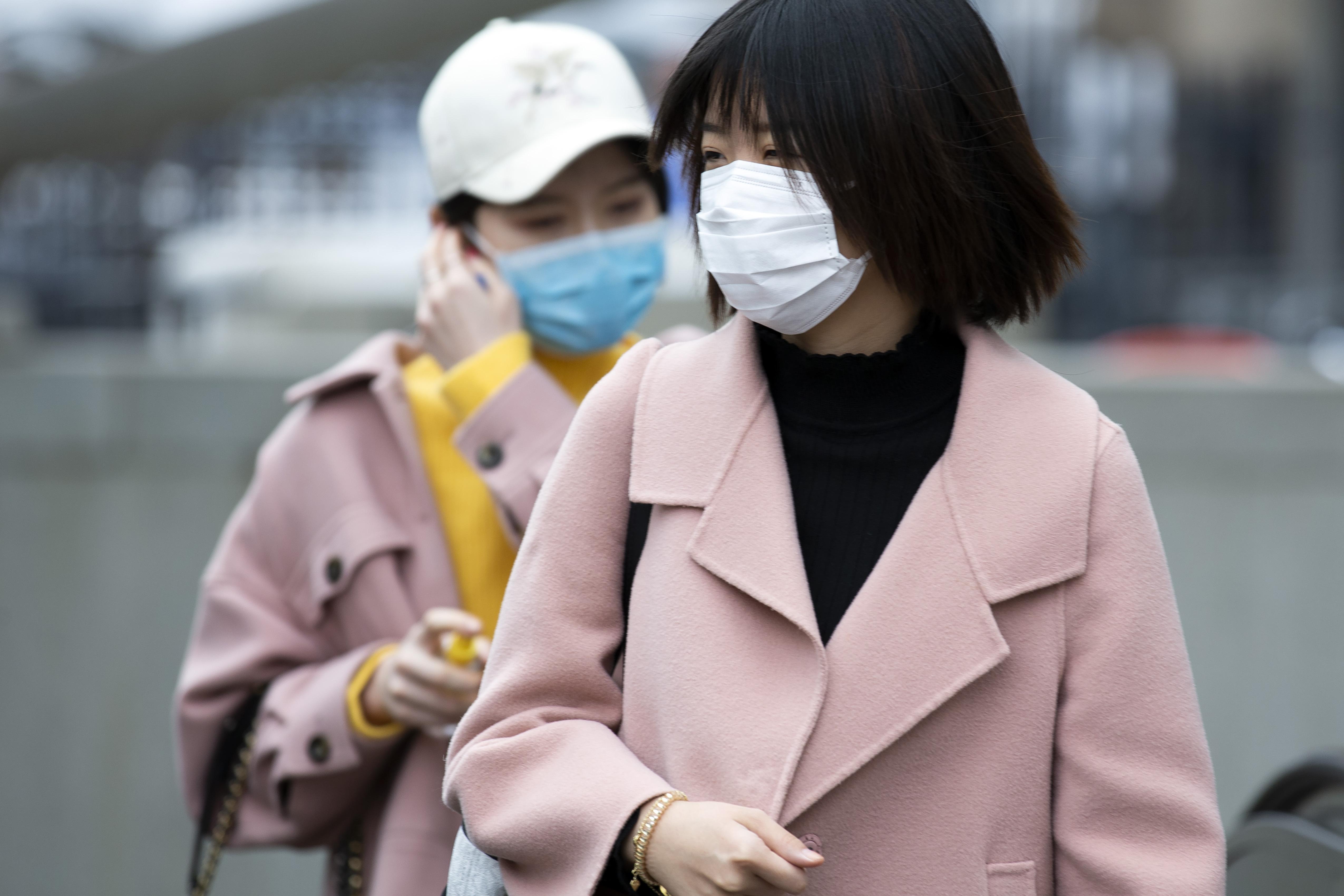 Women wear masks as they exit the Metro subway at George Washington University in Washington, Wednesday, March 11, 2020.