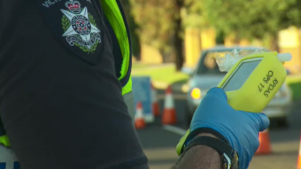 A Victoria Police officer prepares to deliver a roadside alcohol breath test. (9NEWS)